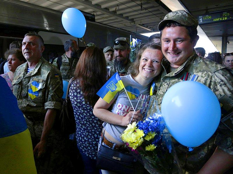 A Ukrainian servicemen hugs a woman holding a Ukrainian flag during a meeting ceremony at the railway station in Kiev. (AFP Photo)