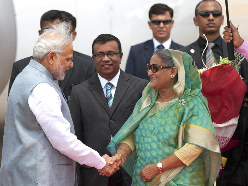 Bangladesh's Prime Minister Sheikh Hasina shakes hand with Narendra Modi upon his arrival at the Hazrat Shahjalal International airport in Dhaka, Bangladesh. (AP Photo)