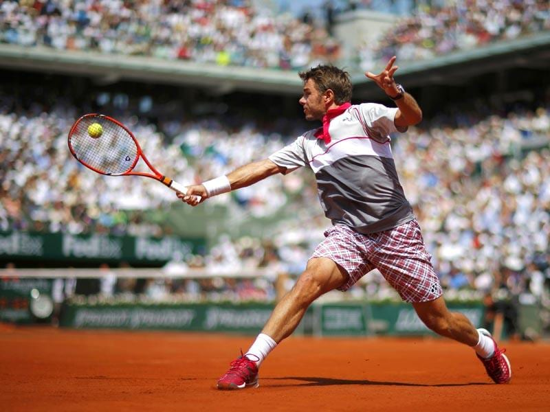 Stan Wawrinka of Switzerland slides on the clay to hit a backhand slice return against Novak Djokovic of Serbia during the men's singles final of the French Open in Paris, France. (Reuters Photo)