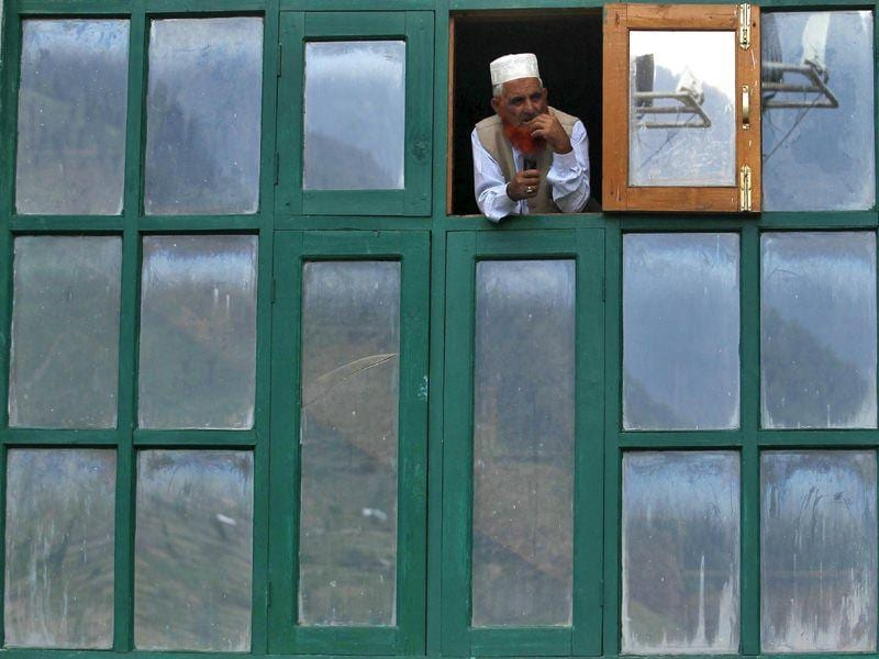A member of the Kashmir Gujjar community looks out from the window of a mosque in Baba Nagri, east of Srinagar on Monday. Reuters Photo