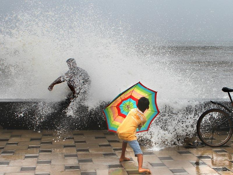 A child shields himself from the high tide at Worli sea face, in Mumbai. The city witnessed heavy rainfall. (Arijit Sen/HT photo)