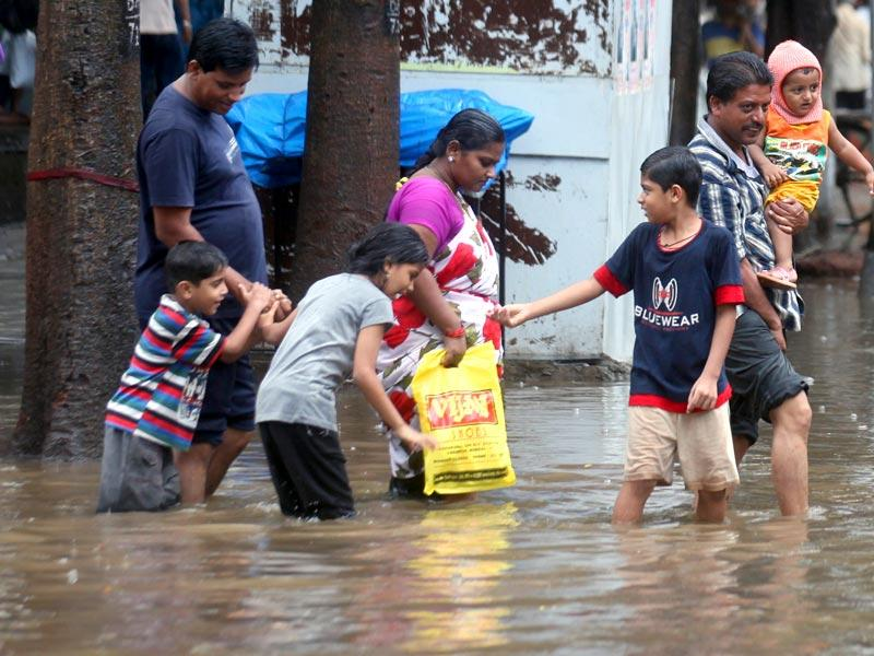 People walk through a flooded street at Hindmata, Dadar as heavy rains lashed Mumbai. (Kunal Patil/HT photo)