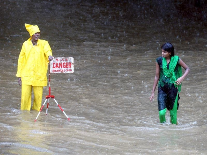 Girl wades through a flooded street at Parel, in Mumbai. (Kunal Patil/HT photo)
