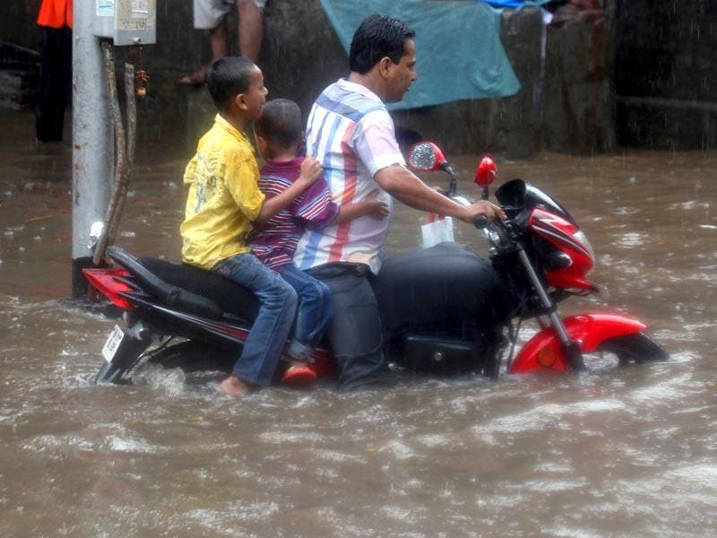 A man wades his bike through a flooded street at Hindamata, Dadar as heavy rains lashed Mumbai. (Kunal Patil/HT photo)