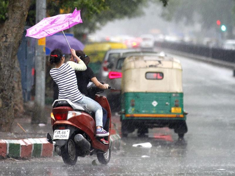 Girls escaping the rain near Connaught Place during the late afternoon shower. (Virendra Singh Gosain/ HT Photo)