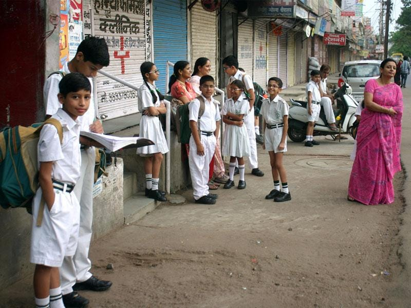 Students wait for their school bus on the first day of the new academic session in Bhopal on Monday. (Bidesh Manna/HT photo)