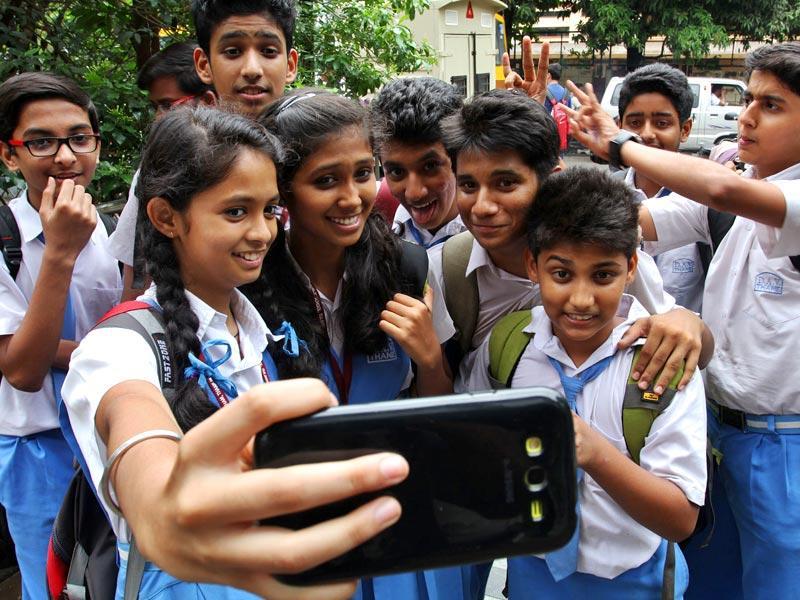 Students take selfies on the first day of school in Thane. (Photo: Praful Gangurde)