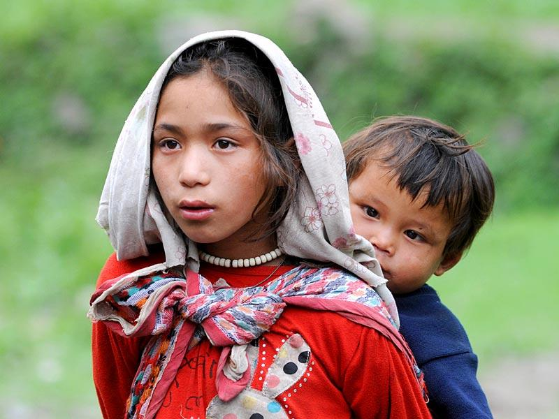 Nepalese child Tharni Guring (L) carrying her younger brother in the village of Sirdibas in Gorkha District. (AFP photo)