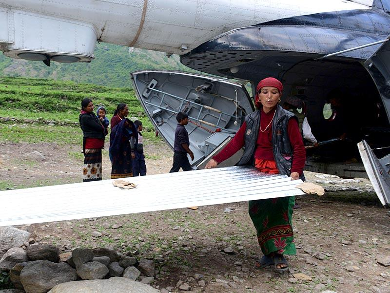 Nepalese villagers unloading a zinc sheet as relief material arrives by helicopter in the village of Sirdibas in Gorkha District, some 250kms north-west of Kathmandu.(AFP photo)