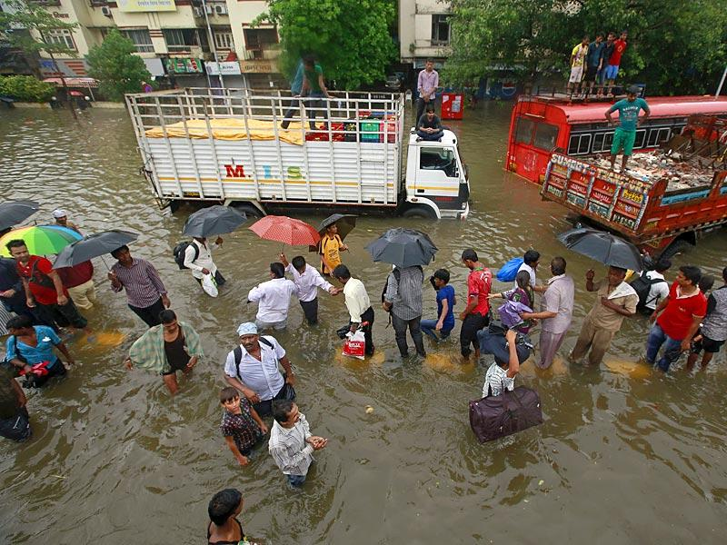 People walk through flooded roads as vehicles are seen stuck in a traffic jam due to heavy rains in Mumbai (Reuters Photo)