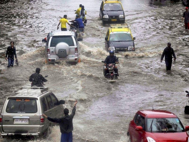 People wade through a water logged road after heavy rains near Dadar in Mumbai (PTI Photo)