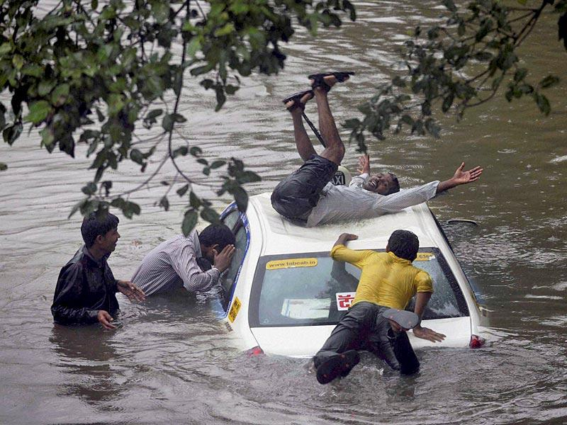 A vehicle stuck in rain water at a road as boys having fun after heavy shower in Mumbai (PTI Photo)