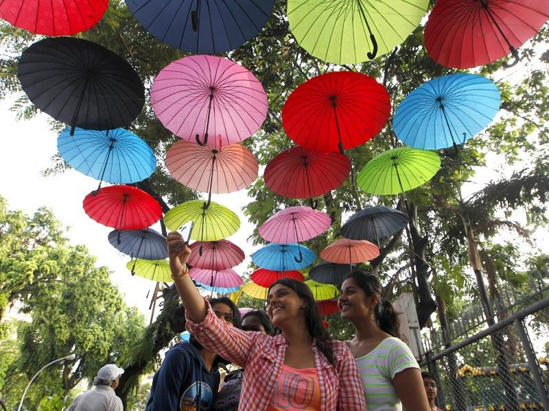 Young visitors take selfies under an umbrella installation at Mumbai's Selfie point. (Kunal Patil/HT photo)