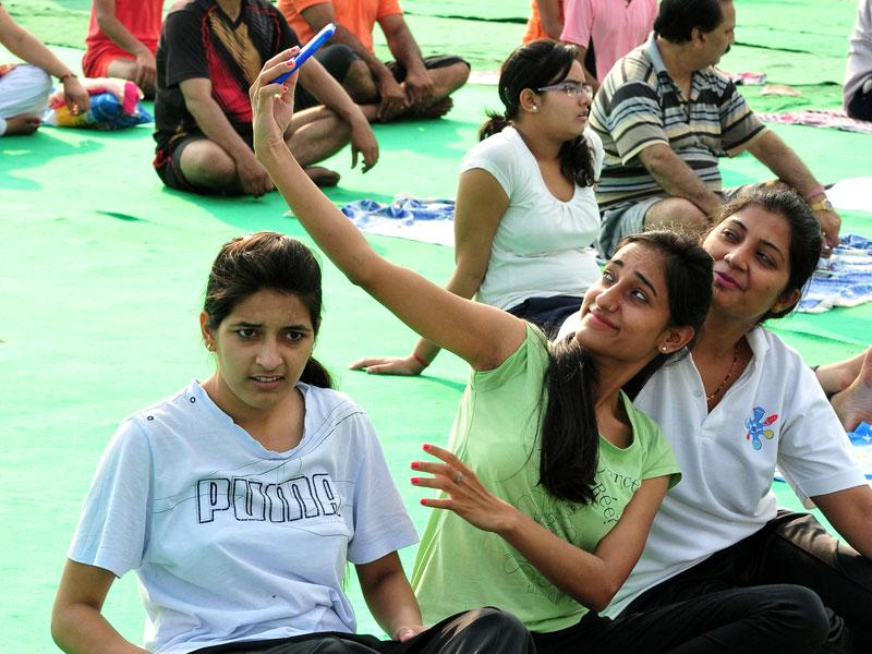 Girls taking a selfie while performing yoga at Exhibition Ground Sector 34 in Chandigarh on Sunday. (Keshav Singh/HT Photo)
