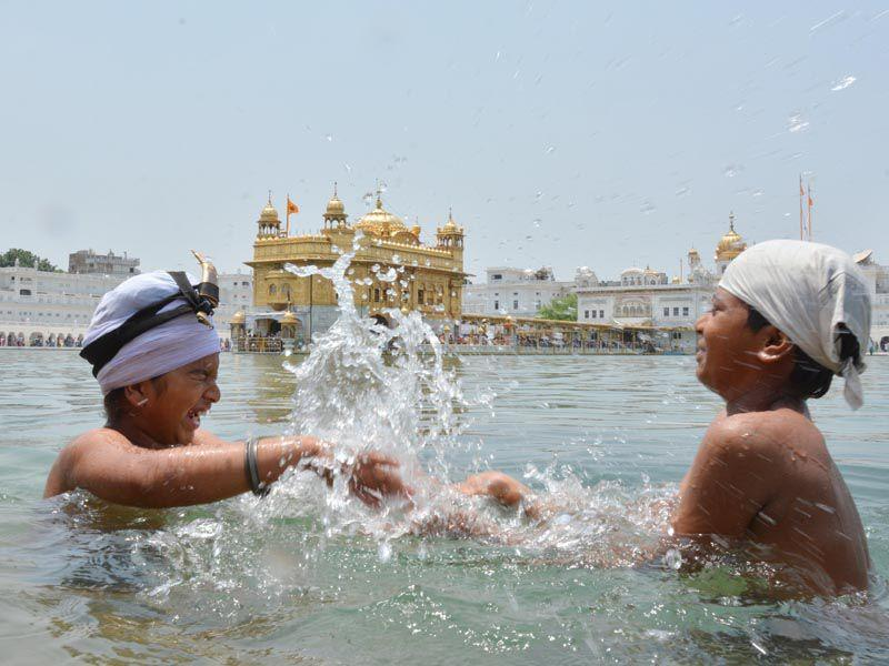 Children enjoying the Holy Dip at the Golden temple while getting relief from the sweltering heat in Amritsar on Sunday. Sameer Sehgal/HT
