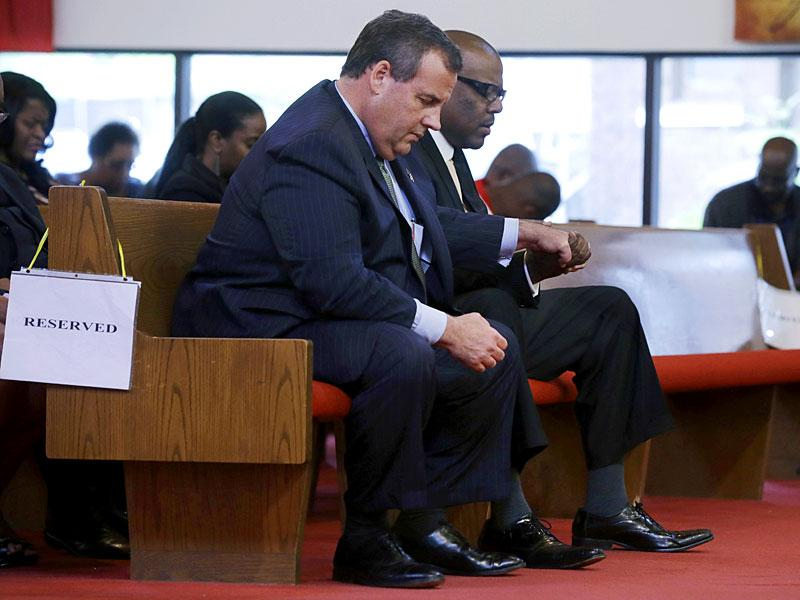 New Jersey governor Chris Christie, left, and Dwayne D Warren, mayor of Orange, NJ, hold hands during a service at St. Matthew African Methodist Episcopal Church. (AP Photo)