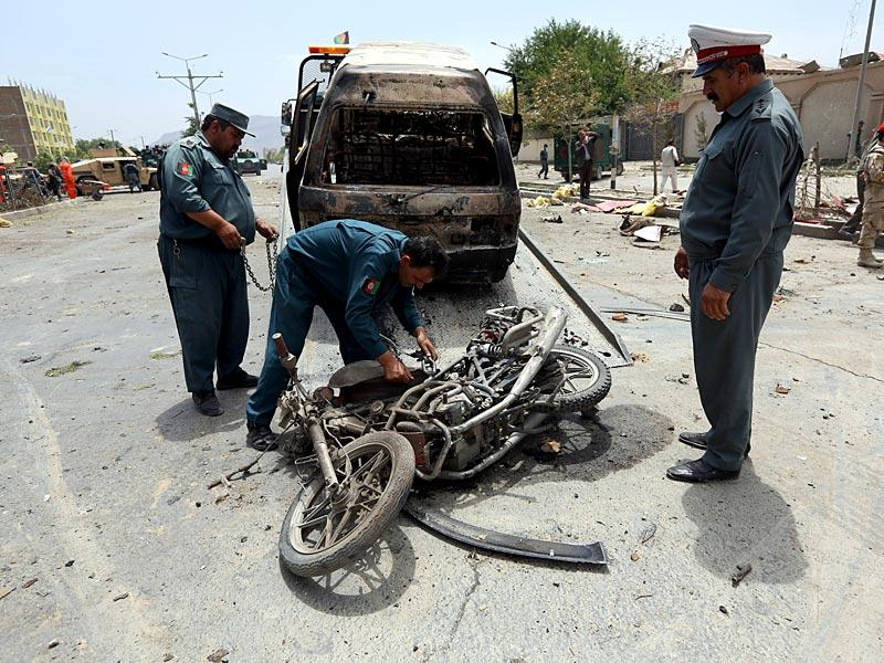 Afghan security forces inspect damages at the site of the suicide attack outside the Parliament building in Kabul. (AP Photo)