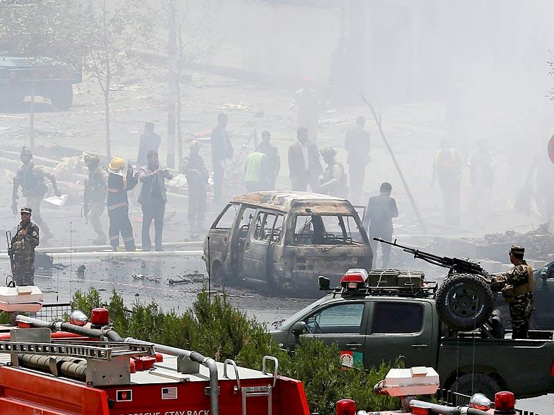Members of security forces stand at the site of the attack. A Taliban suicide bomber and six gunmen attacked the Afghan Parliament, wounding at least 19 people and sending a plume of black smoke across Kabul. (Reuters Photo)