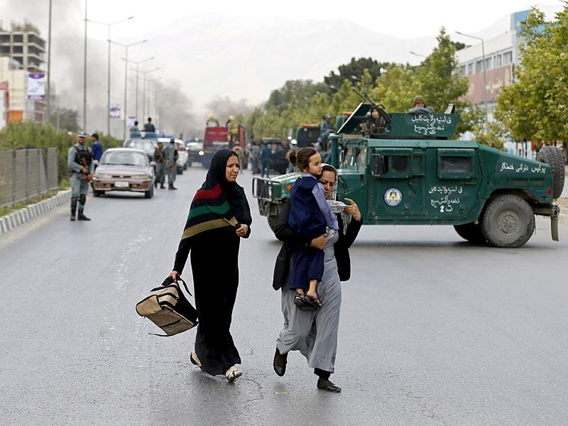 Women walk past as smoke rises from the site of the suicide attack near the Afghan Parliament. (Reuters Photo)