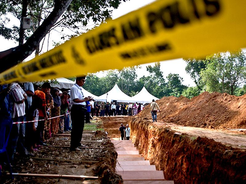 A Malaysian Muslim man looks on as he stands near a pit during the re-burial of remains believed to be those of ethnic Rohingya found at human-trafficking camps (AFP Photo)