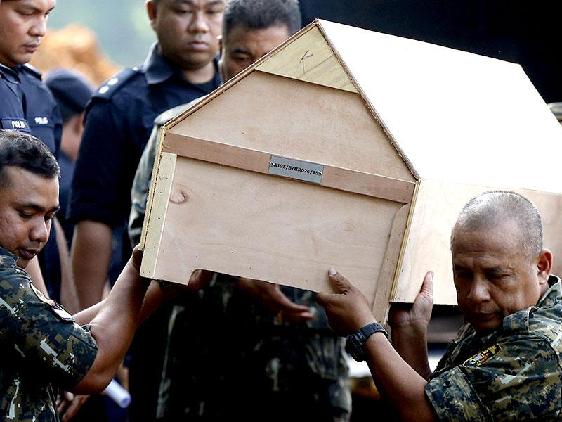 Malaysian police carry a coffin with unidentified remains of Rohingya people found at a traffickers camp in Wang Kelian (Reuters Photo)