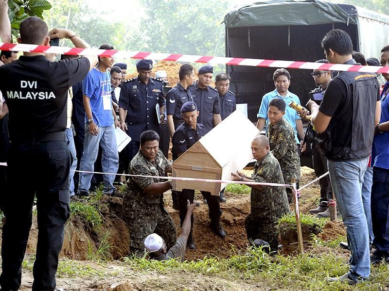 Malaysian police carries a coffin containing the remains of a Rohingya migrant for a mass burial ceremony (AP Photo)
