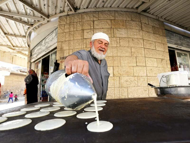 A man makes traditional sweets in a market in the town of Ramtha, Jordan. (Reuters Photo)