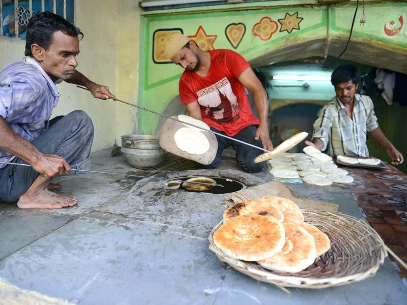 "Muslim bakers prepare a version of naan bread popularly known as ""Khadeem Munshai Naan"" in Hyderabad. (AFP PHOTO)"