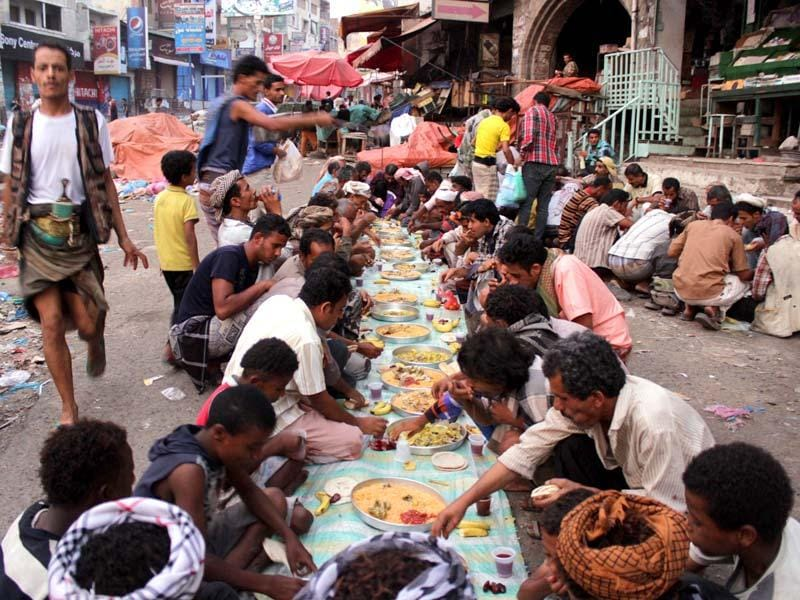 Yemenis break their fast as they gather in the street to eat in the southern Yemeni city of Taez..( AFP PHOTO )