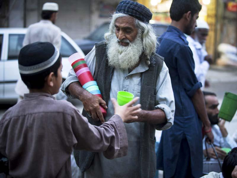 A Pakistani volunteer provides cups for cold water or milk provided for the iftar meals in Rawalpindi, Pakistan. (AP Photo)