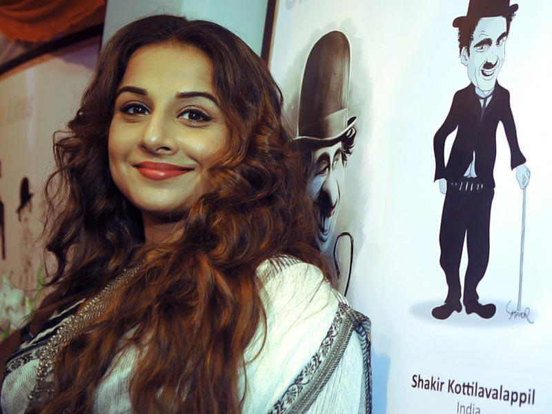 Vidya Balan rests on a portrait of Charlie Chaplin at