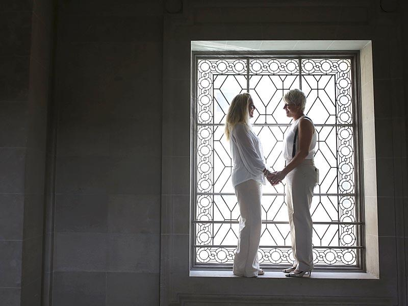 Stacy Wood (L) and her wife Michele Barr pause between wedding photos at San Francisco City Hall after getting married in San Francisco, California. The Supreme Court ruled 5-4 that the Constitution's guarantees of due process and equal protection under the law mean that states cannot ban same-sex marriages. (Reuters)