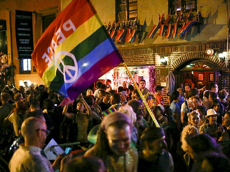 People celebrate outside the Stonewall Inn, late in the night in the Greenwich Village neighborhood of New York. With the SC ruling, gay marriage will become legal in all 50 US states. (Reuters)