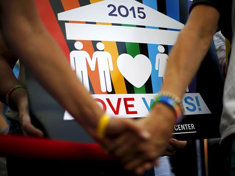 A couple hold hands at a celebration rally in West Hollywood, California. (Reuters)