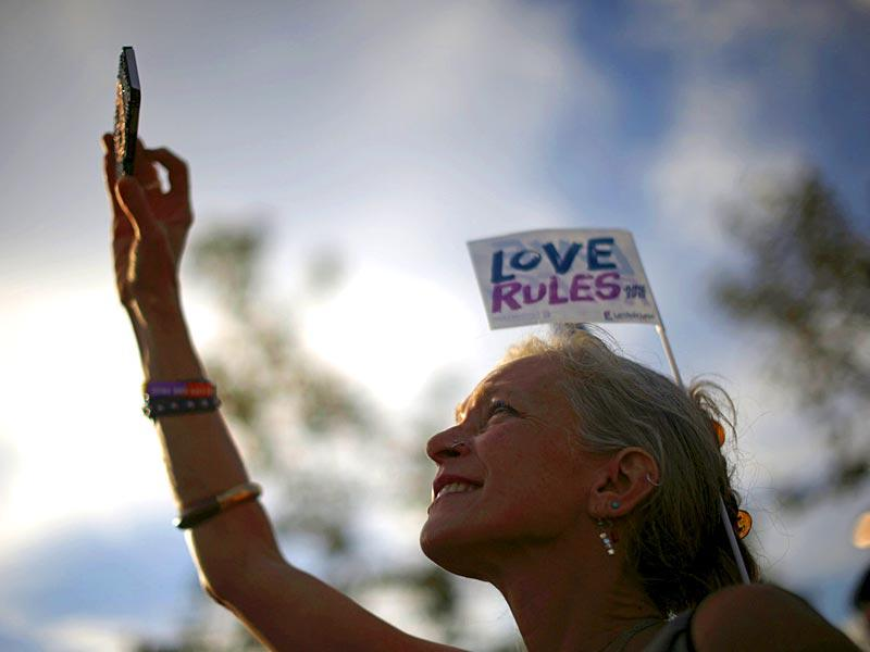 A woman takes a photo at a celebration rally in West Hollywood, California. (Reuters)