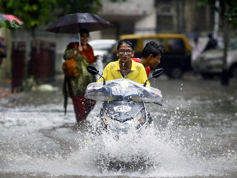 A boy rides through a waterlogged lane at Dadar, in Mumbai. (HT photo/Arijit Sen)