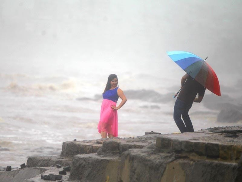A woman poses for a picture in the rain at Carter Road in Mumbai. (Satish Bate/HT photo)
