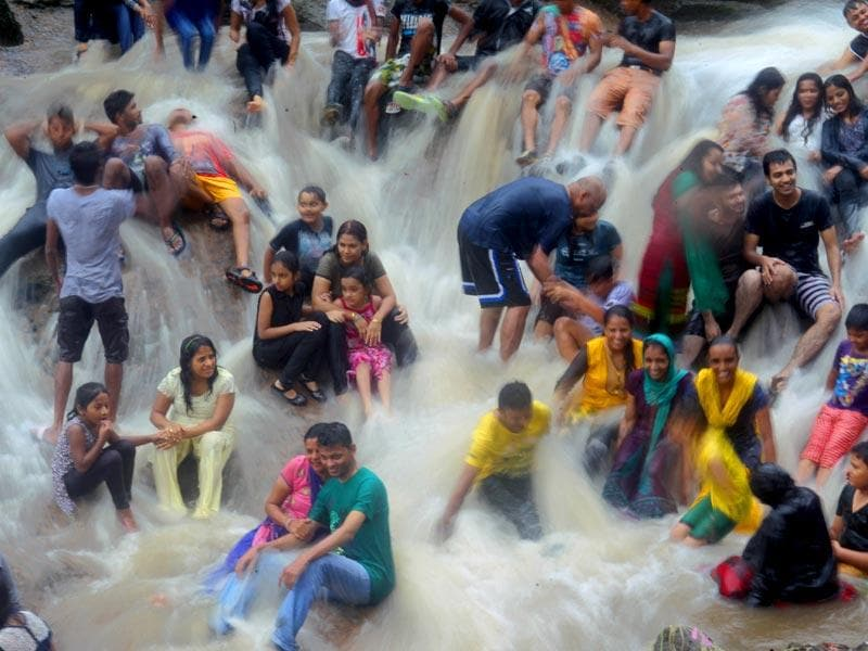 People enjoy the waterfall at Kanheri caves in Mumbai. (Satish Bate/HT photo)