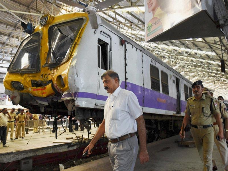 Officials and policemen inspect the accident site after a Mumbai local train got derailed when its driver lost control at the Churchgate station (PTI Photo)
