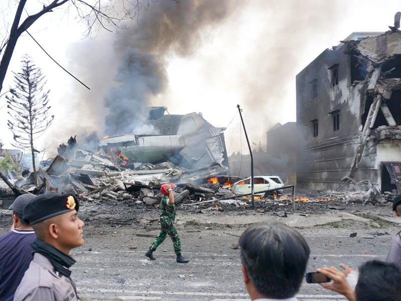Indonesian police and military officials secure the crash site of military Hercules plane in Medan, North Sumatra province. (AFP Photo)