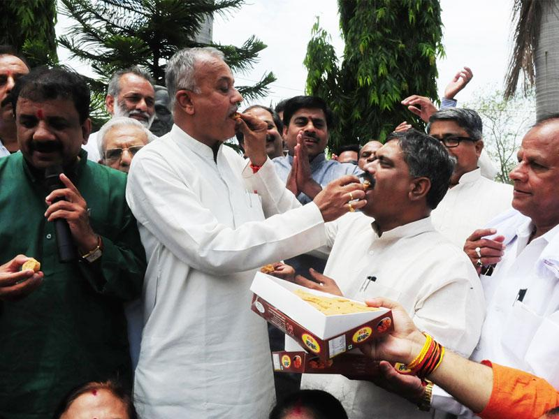BJP state president Nand Kumar Singh Chauhan shares sweets with party men to celebrate party's win in Garoth by-poll, in Bhopal on Tuesday. (Mujeeb Faruqui/HT)