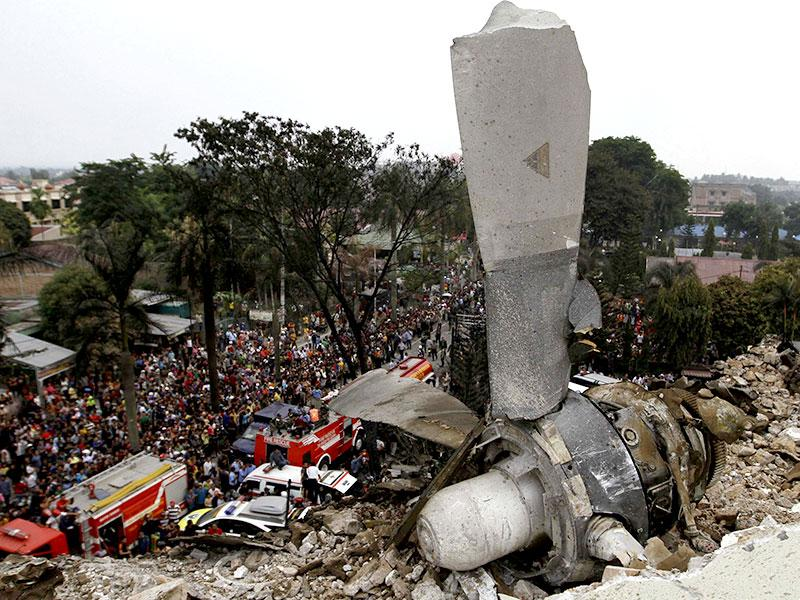 A propeller from an Indonesian military C-130 Hercules transport plane rests on the roof of a building (Reuters Photo)