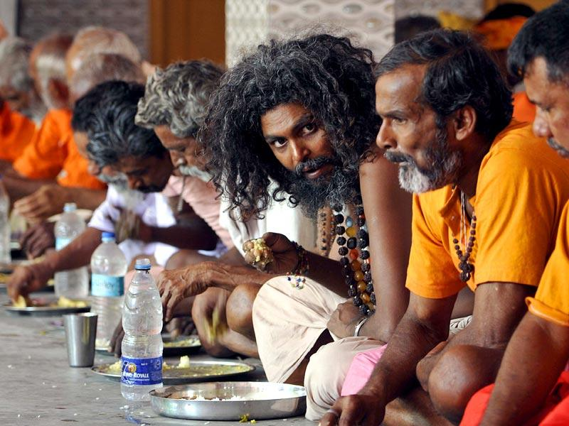 Sadhus eat a meal at a community kitchen at a temple in Jammu before registering their names for the yatra. (Nitin Kanotra/ HT Photo)