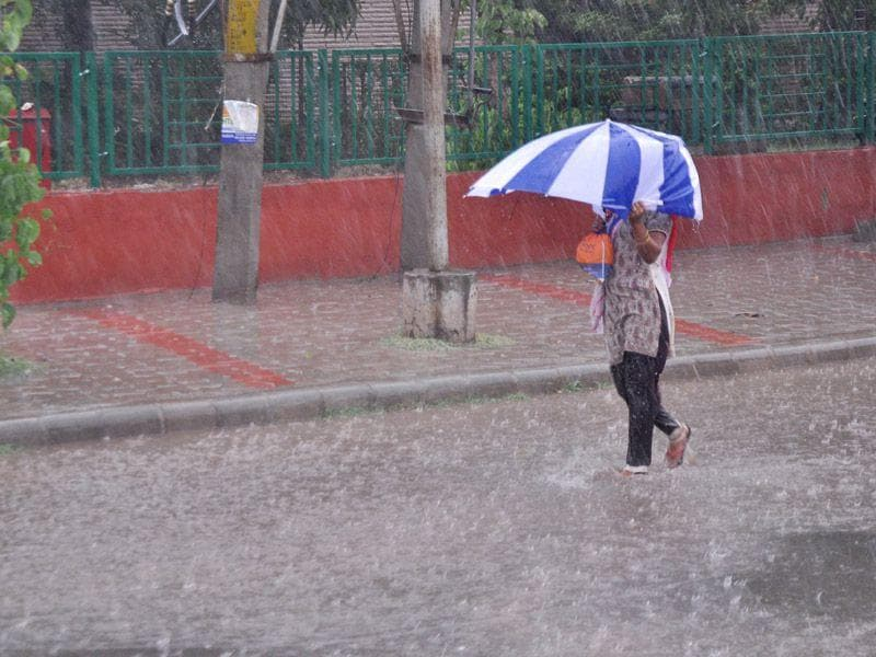 A woman shielding herself with umbrella in Panchkula. Sant Arora/HT
