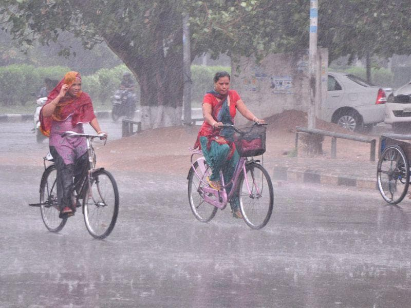 Women cycling during the rainfall in Panchkula on Thursday. Sant Arora/HT