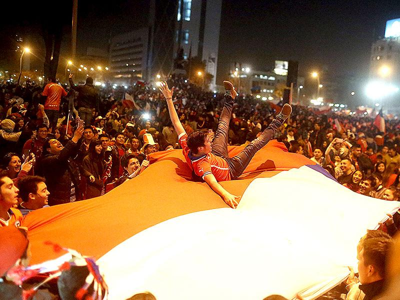 A fan jumps on a giant Chilean national flag during celebrations on the street following Chile's victory over Argentina in their Copa America final soccer match in Santiago, Chile July 4, 2015. (Reuters Photo)
