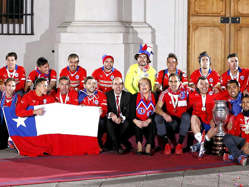 Chile's president Michelle Bachelet and Chile's national soccer team pose with the Copa America trophy at the La Moneda presidential palace. (Reuters Photo)