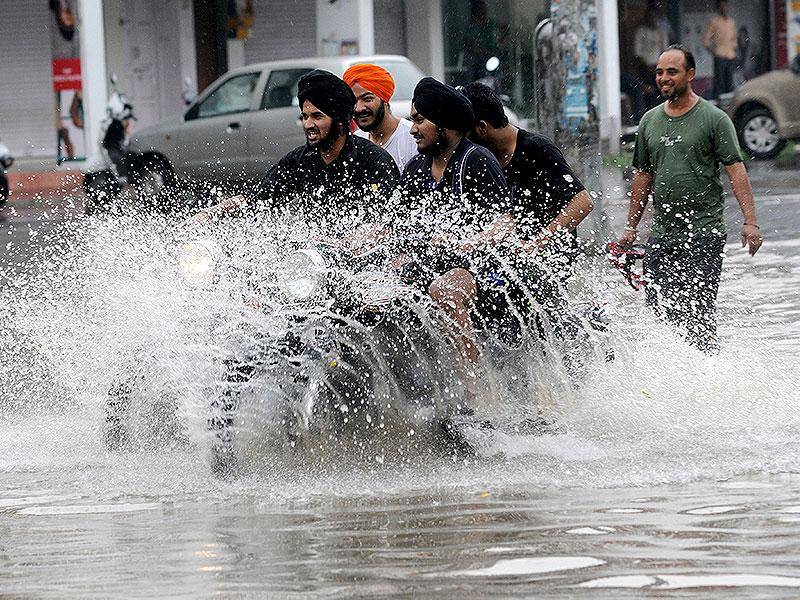Drivers struggle to get through the waterlogged streets of Mohali, after a sudden burst of heavy rainfall across North India. (HT Photo)