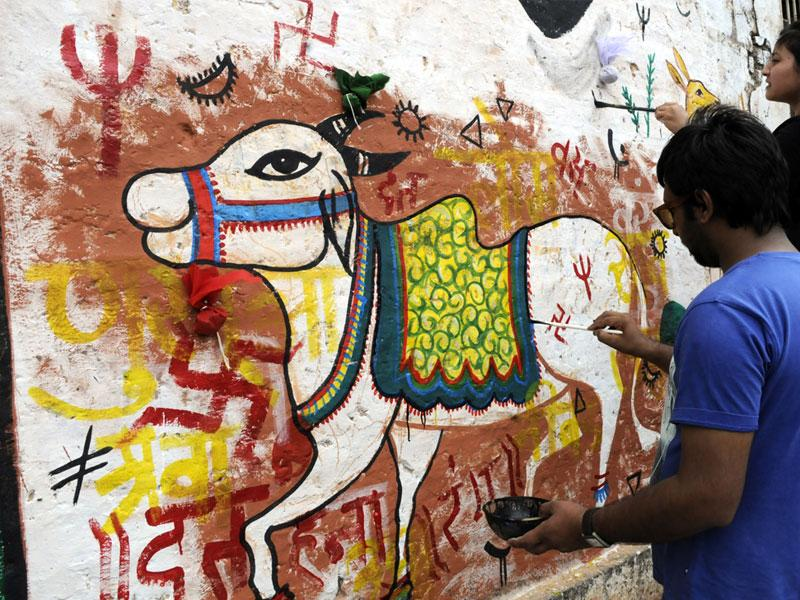 Indore residents and students of Government Fine Arts College paint old, dilapidated walls along MG Road in Indore. (Shankar Mourya/HT photo)