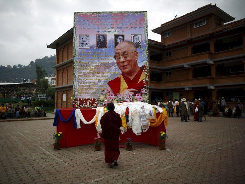 A Tibetan monk offering prayers in front of the portrait of Dalai Lama during his 80th birthday celebration in Kathmandu. Reuters
